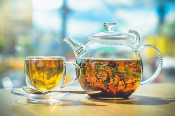 A glass teapot with tea and a glass cup with tea stand on the table