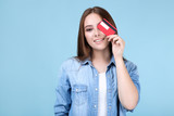 Young woman holding credit card on blue background - 286372932