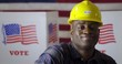 """Close up African American man in plaid shirt puts on hard hat with """"I Voted"""" sticker while profile to camera, then turns. smiling in front of polling booths with US flag. Large US flag behind"""