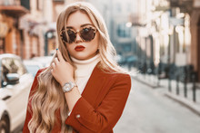 Outdoor Close Up Street Fashion Portrait Of Young Elegant Woman Wearing Trendy Autumn Outfit: Turtle Frame Sunglasses, Luxury Wrist Watch, Terracotta Color Blazer, White Classic Turtleneck. Copy Space