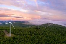 Wind Turbines On Mountain Ridge At Sunset With Rainbow