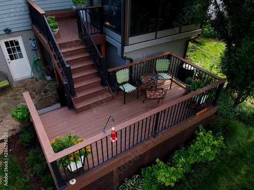 Fototapeta View of a landscaped back yard with a new composite deck and sunroom obraz