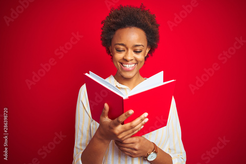 Fotografie, Obraz African american woman reading a book over red isolated background with a happy