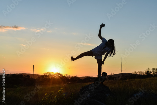 Silhouette girl playing in the sun. Wallpaper Mural