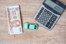 Thai Baht Banknote Stack With Car And Calculator Background. Business, Money, Car For Cash And Car Insurance Concept