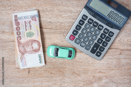 Obraz na plátne Thai baht banknote stack with Car and calculator background