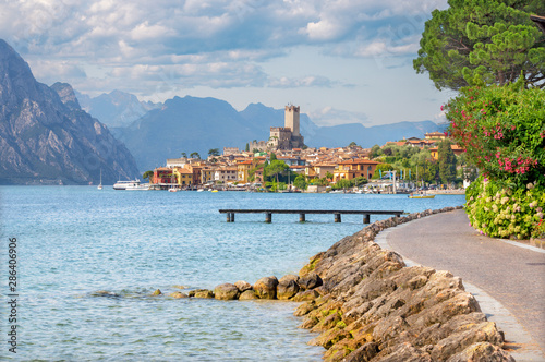 Obraz Malcesine - The promenade over the Lago di Garda lake with the town and castle in the background. - fototapety do salonu
