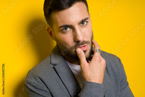 Young handsome man possing and modeling over yellow isolated background
