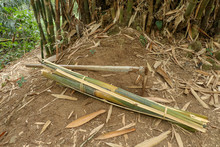 Bamboo Laths Tied In Burrs. A Hoe And A Bundle Of Chopped Bamboos Lie On Clay Ground Among The Withered Leaves. Simple Working Tools Of Balinese Farmers For Handwork On Bali Island In Indonesia.