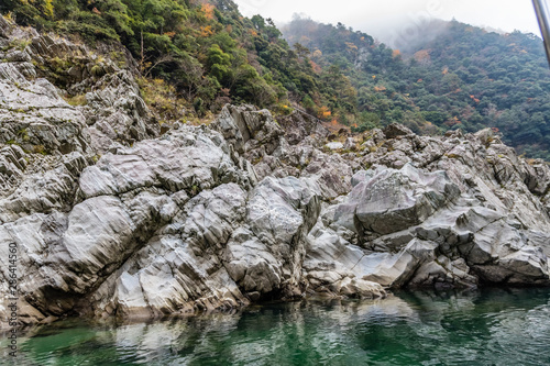 Stone next to a deep green river with striations and smoothed from water on the Canvas-taulu