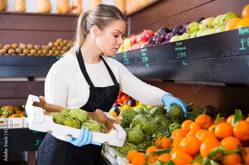 Photo sur Toile Les Textures Salesgirl arranging goods in greengrocery