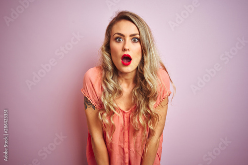 Young beautiful woman wearing t-shirt standing over pink isolated background afraid and shocked with surprise and amazed expression, fear and excited face Wallpaper Mural