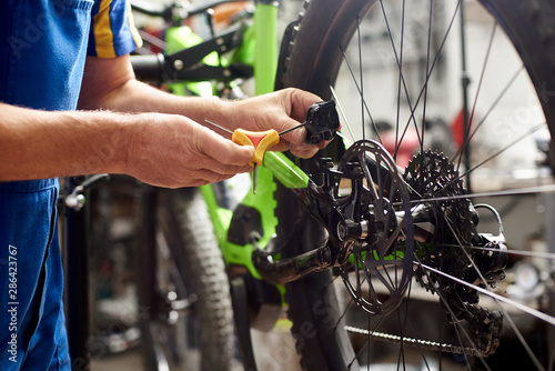 Cropped shot of male mechanic making service in bicycle