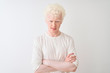 Leinwanddruck Bild - Young albino blond man wearing casual t-shirt standing over isolated white background skeptic and nervous, disapproving expression on face with crossed arms. Negative person.