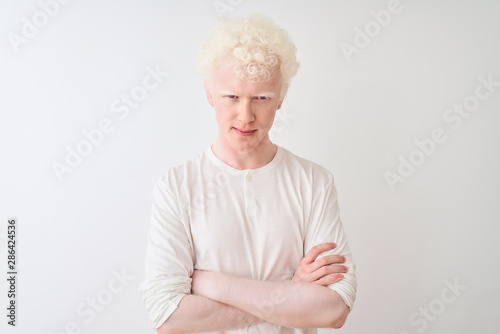 Photo Young albino blond man wearing casual t-shirt standing over isolated white background skeptic and nervous, disapproving expression on face with crossed arms