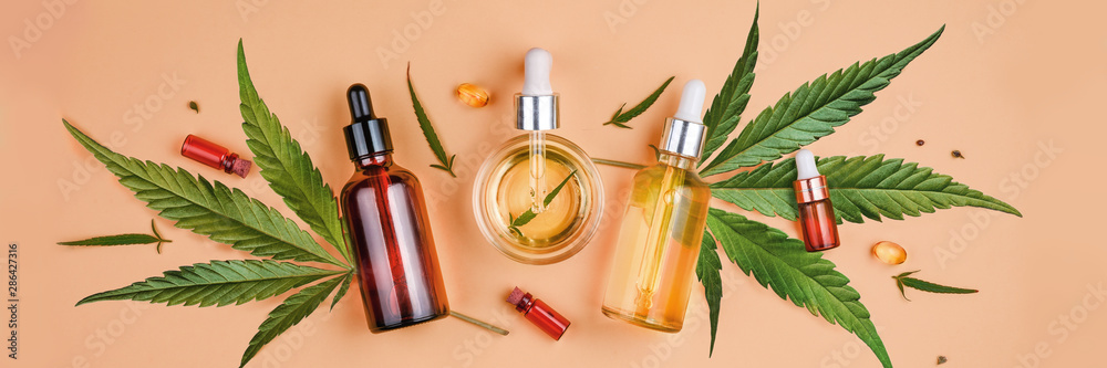 Fototapeta Different glass bottles with CBD OIL, THC tincture and cannabis leaves on yellow background. Flat lay, minimalism. Cosmetics CBD oil.
