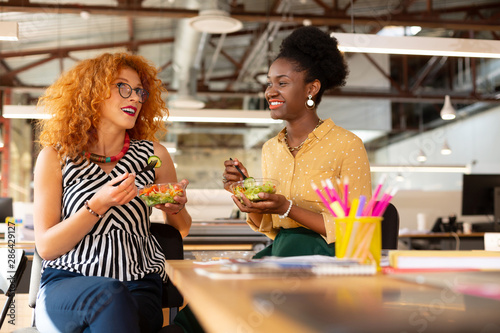 Photo  Curly businesswoman eating salad with dark-skinned colleague