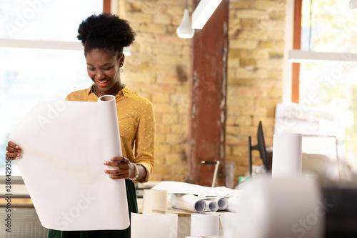 Dark-skinned worker of publishing agency holding roll of paper