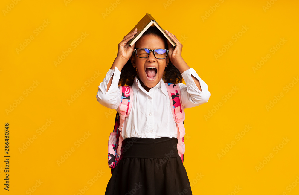 Fototapeta Overwhelmed Black School Student Girl Shouting Covering Head With Book