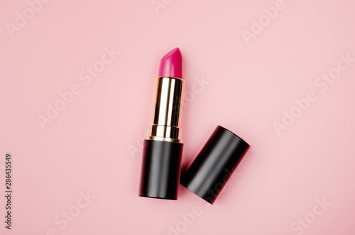 Fotografiet  Pink lipstick tube, lip gloss top view