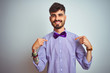 canvas print picture - Young man with tattoo wearing purple shirt and bow tie over isolated white background looking confident with smile on face, pointing oneself with fingers proud and happy.