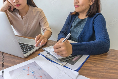 Two woman having discussion in front of laptop and documents Wallpaper Mural