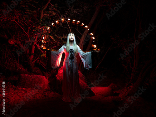 Fotografie, Obraz  A woman sitting on a rock in the forest and dressed in a tunic, throws red lights from her hands