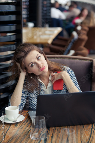 Photo beautiful serious young business woman sitting at a table in restaurant