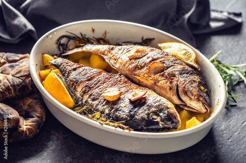 Fotografie, Obraz  Roasted mediterranean fish bream with potatoes rosemary and lemon