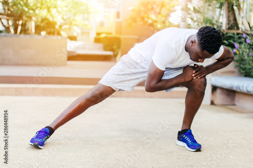 Athletic African American man in blue sneakers doing stretching exercise while t Canvas Print