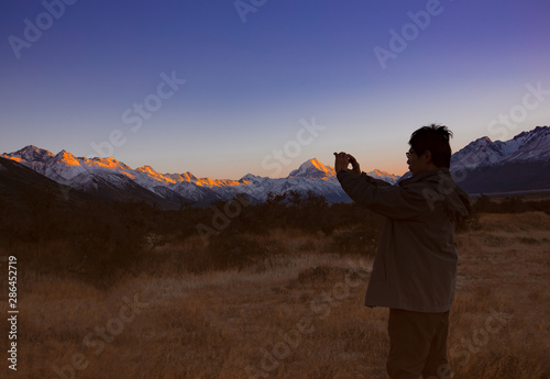 Fototapeta Happy and relax time with smartphone taking picture  in the morning at Mount Cook National Park, South Island, New Zealand obraz na płótnie