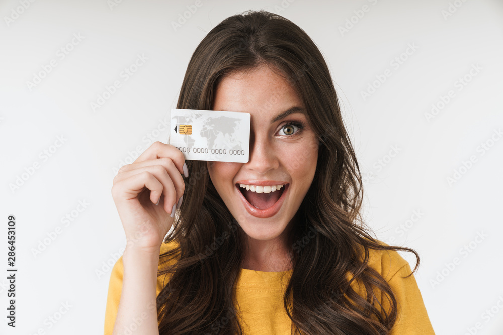 Fototapeta Image of gorgeous brunette woman wearing casual clothes smiling and holding credit card
