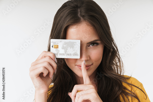 Obraz Image of beautiful brunette woman wearing casual clothes keeping finger at lips and holding credit card - fototapety do salonu