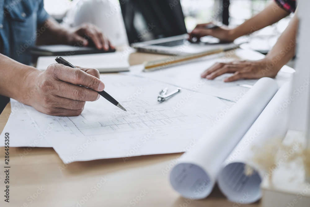 Fototapeta Construction and structure concept of Engineer or architect meeting for project working with partner and engineering tools on model building and blueprint in working site