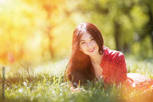 Foto auf AluDibond Gelb Schwefelsäure Young cute woman in red dress relaxing in the autumn park. Beauty nature scene with colorful background, trees at fallseason. Outdoor lifestyle. Happy smiling woman lay on green grass
