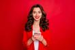Leinwandbild Motiv Portrait of lovely lady using device with beaming smile isolated over red background