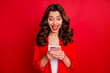 Leinwandbild Motiv Portrait of excited woman using device screaming wow omg wearing bright jacket isolated over red background
