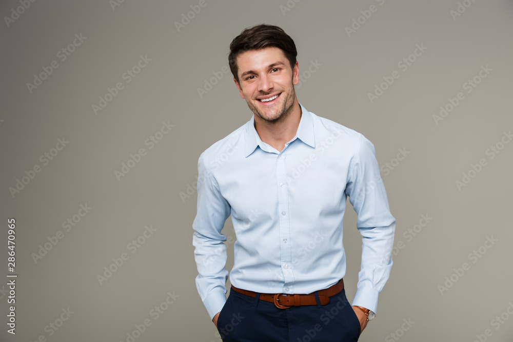 Fototapeta Image of happy brunette man wearing formal clothes smiling at camera with hands in pockets