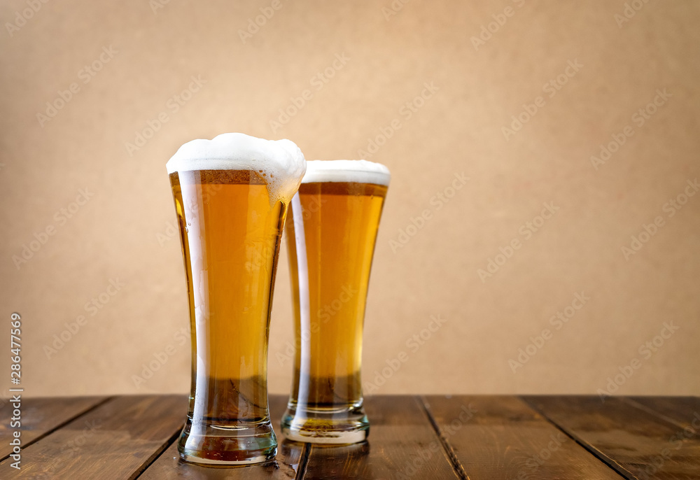 Fototapeta Two light beer glasses w on the light yellow background