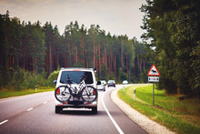 Car Is Moving On The Road Through The Pine Tree Forest With Bicycles On Platform, Moose Warning Sign