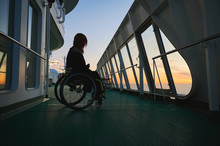 Young Woman In Wheelchair In Sunset On A Cruise Ship