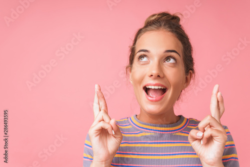 Fototapeta Image closeup of joyful beautiful woman screaming and dreaming with fingers crossed obraz