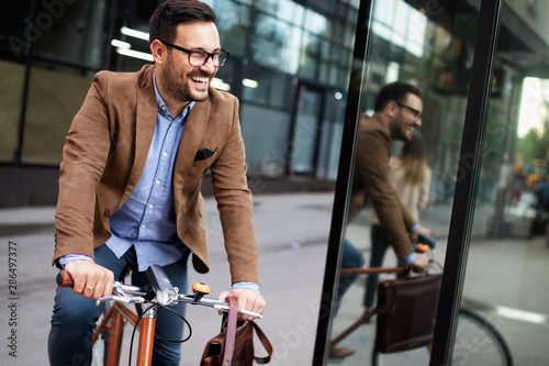 Cuadros en Lienzo Happy young stylish businessman going to work by bike