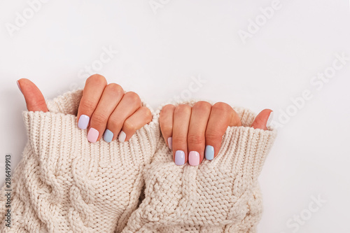 Woman's hands with proffesional manicure in pastel colors
