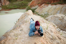 Photographer Traveler Shoots Wildlife With Professional Equipment Lying On The Edge Of A Natural Quarry