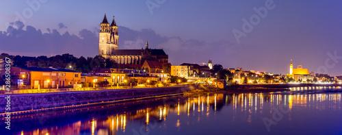 Magdeburg an der Elbe mit Magdeburger Dom, Johanniskirche, mit Promenade am Ufer des Flusses in Abendstimmung mit Abendrot und beleuchteten Gebäuden im Panorama