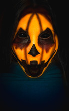 Scary Pumpkin Face Of A Halloween Creature With Opened Mouth On Dark Background