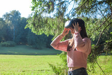 Virtual Forest. A Young Woman In VR Glasses Stands Under The Trees In A Clearing, On Sunny Day, Touches The Air.