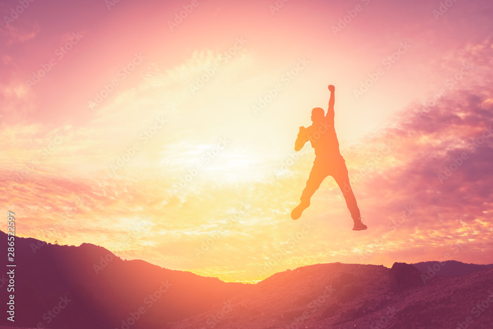 Fototapety, obrazy: Happy man jumping at top of mountain with sunset sky abstract background.