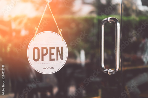 Obraz Open sign hanging front of cafe with colorful bokeh light abstract background. - fototapety do salonu
